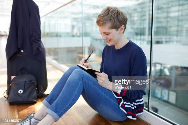Blond businesswoman sitting on ground, writing in notebook
