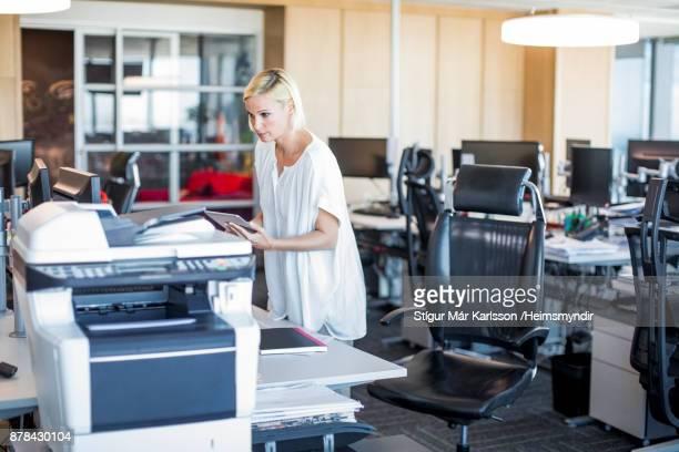 デジタル タブレットを使用してオフィスで金髪の実業家 - 印刷機 ストックフォトと画像