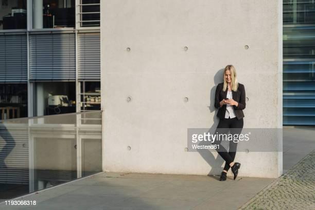 blond businesswoman using smartphone leaning on wall - ビジネスウェア ストックフォトと画像