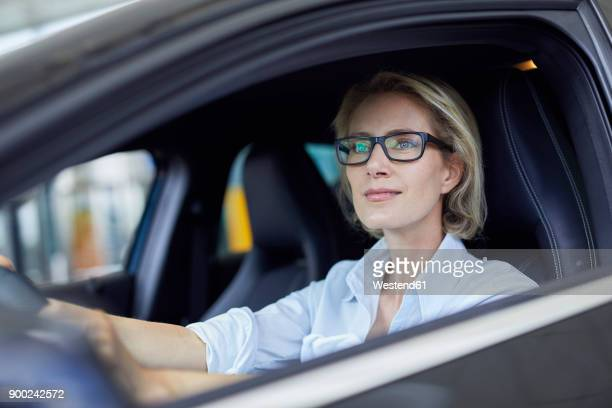 blond businesswoman wearing glasses driving car - driver stock pictures, royalty-free photos & images