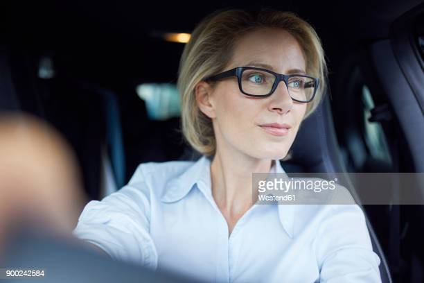 Blond businesswoman wearing glasses driving car