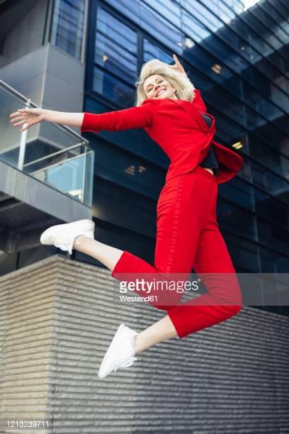 blond businesswoman wearing red suit - geschäftskleidung stock-fotos und bilder