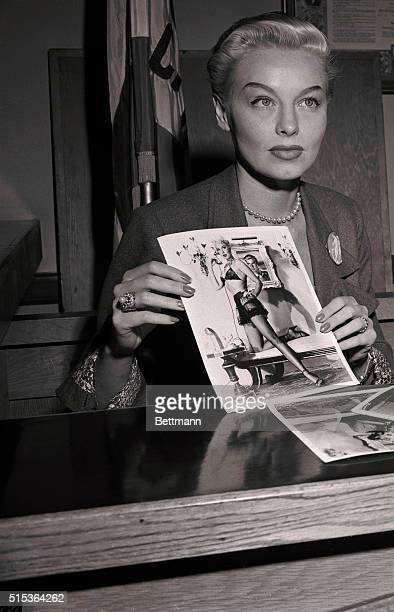 Blond dancer Lili St Cyr shows a predominantly female jury a photograph of herself wearing the costume in which she was arrested for giving a lewd...