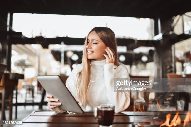 beleza feminina loira fechando os olhos e colocando fone de ouvido para curtir música durante o tempo do chá - cabelo liso - fotografias e filmes do acervo