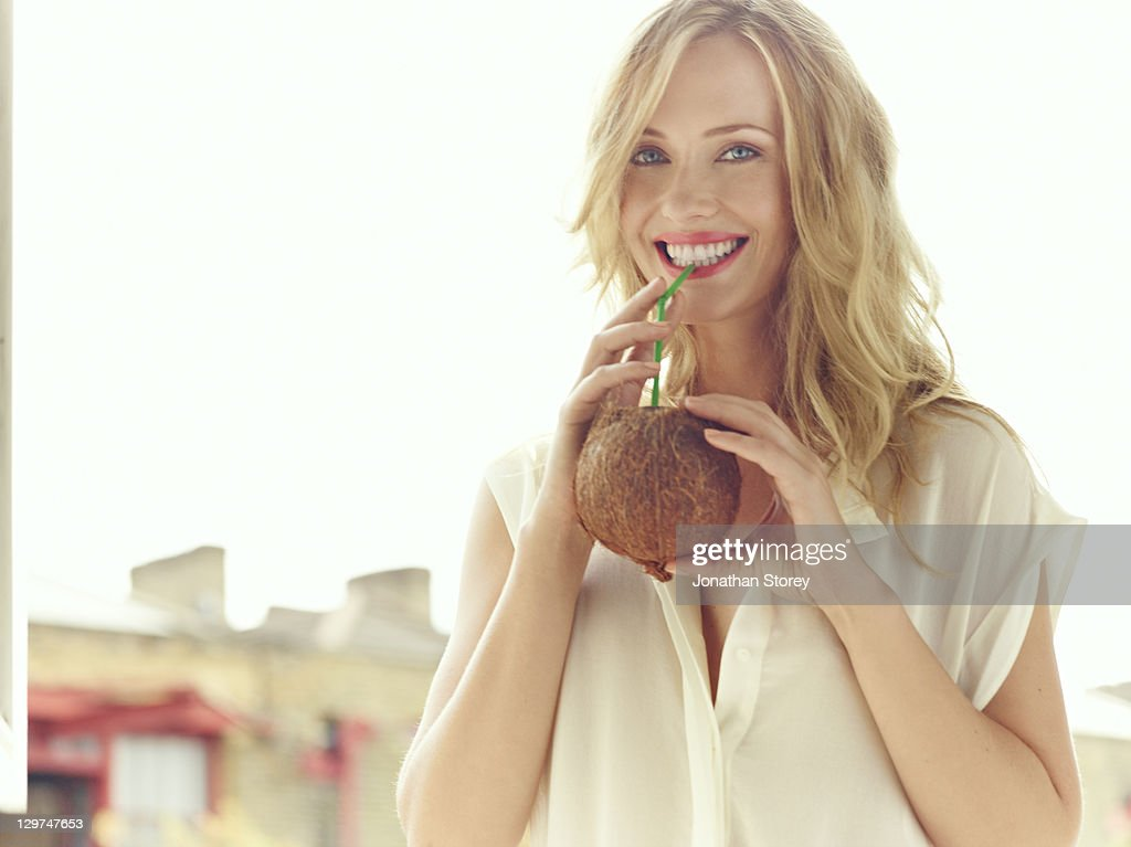 Blond female drinking from a coconut. : Stock Photo