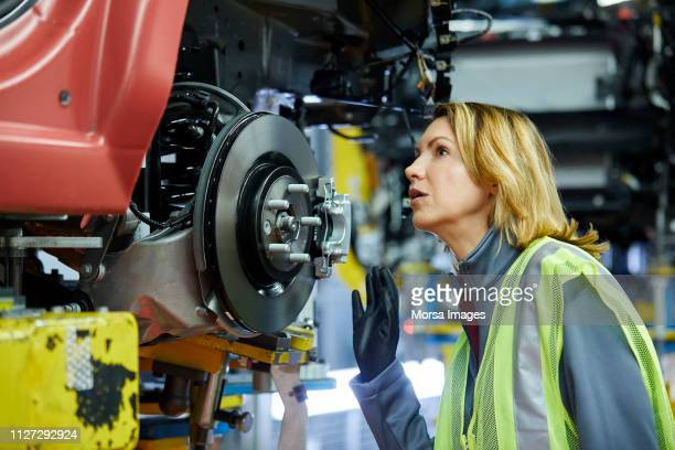 blond female engineer checking vehicle at factory - mechanical engineering stock pictures, royalty-free photos & images