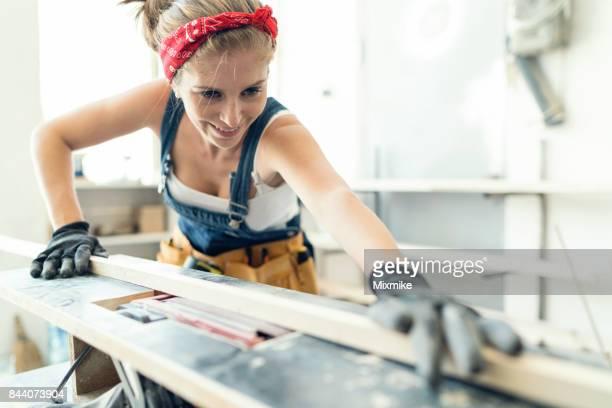 Blonde Frau Schleifen eine hölzerne Latten in der Werkstatt