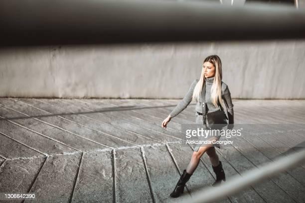 blond wijfje in elegante kleding die in stedelijk gebied buiten loopt - rok stockfoto's en -beelden