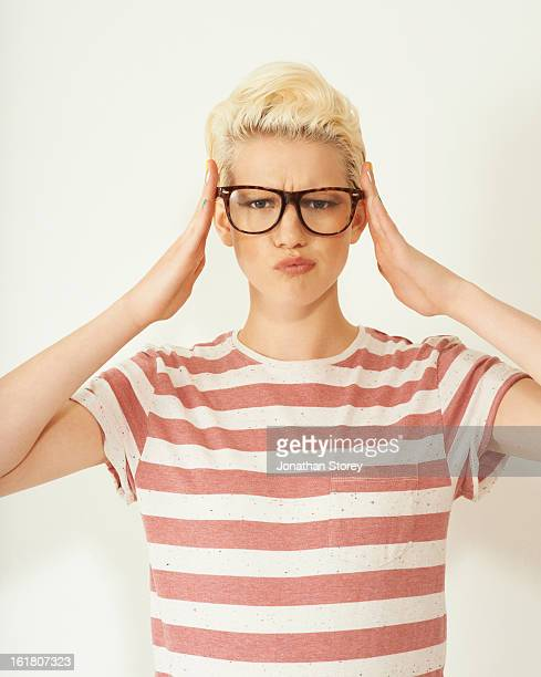 Blond female pushing her reading glasses on
