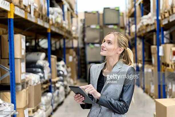 Blond female worker touching digital tablet at warehouse