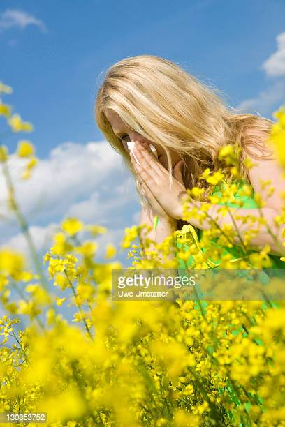 Blond girl blowing her nose while standing in a field of rape