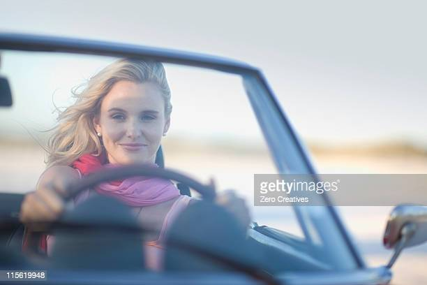 Blond girl driving a cabriolet