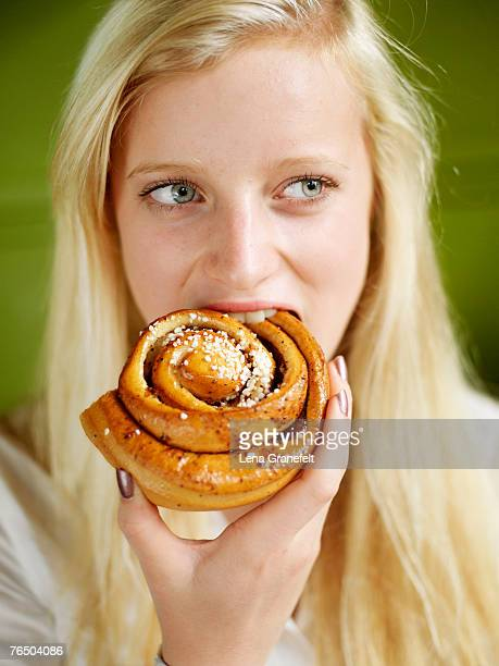 A blond girl eating a bun.