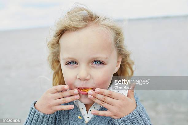 Blond girl eating chips on the beach