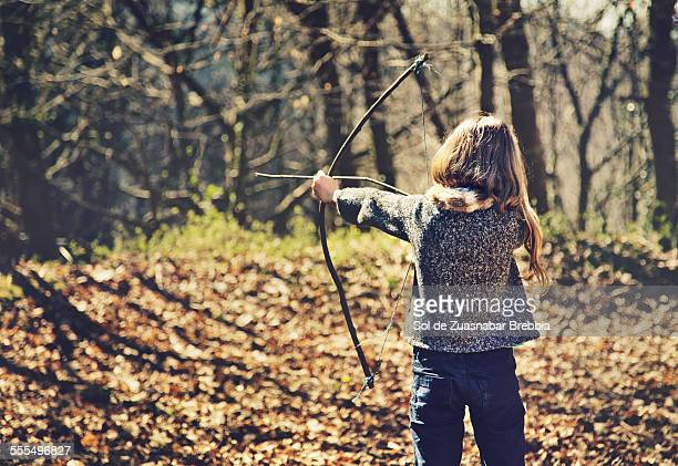 Blond girl in a forest with a wooden bow and arrow