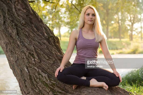 Blond girl in lotus position sitting on a tree