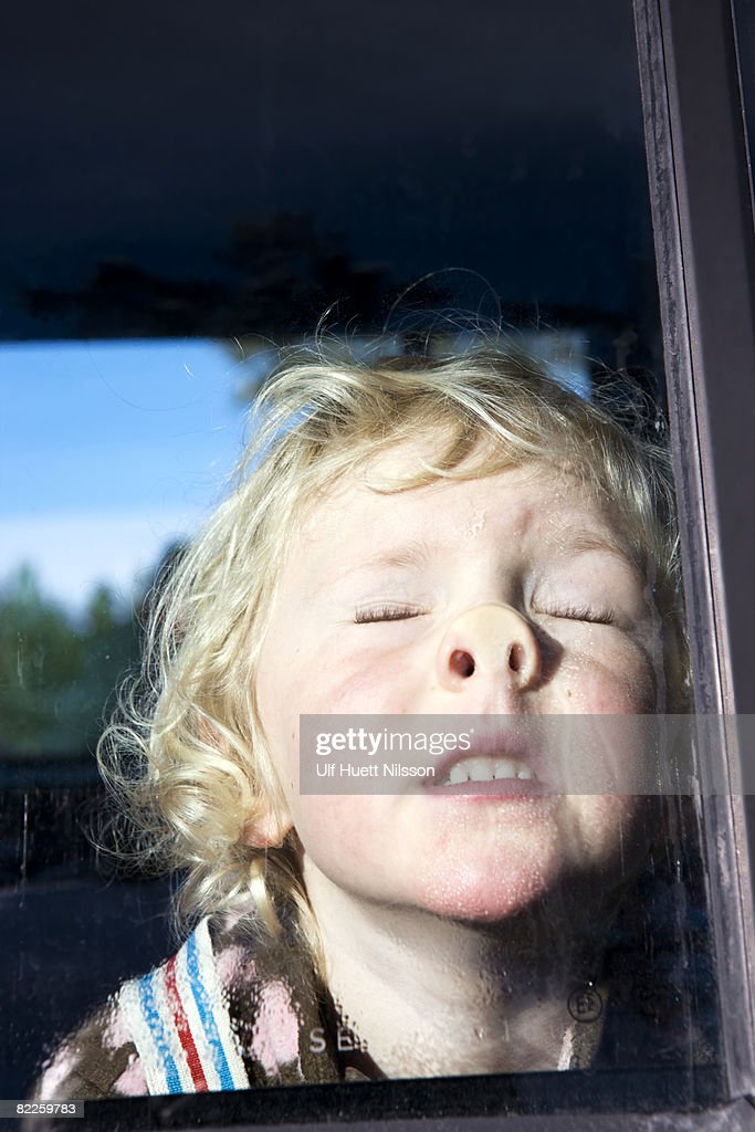 A blond girl pushing her face against a window. : Stock Photo