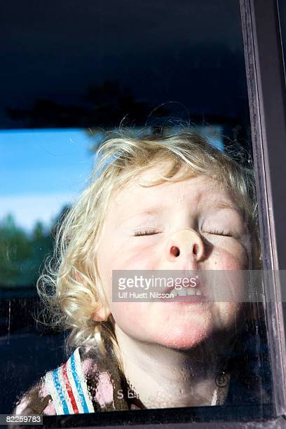a blond girl pushing her face against a window. - grimassen stockfoto's en -beelden