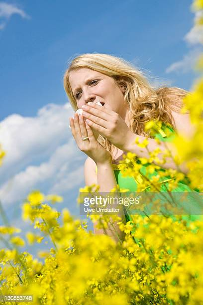 Blond girl sneezing while standing in a field of rape
