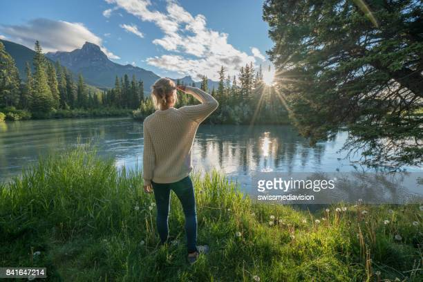 blond girl watching sunrise from river bank - pinaceae stock photos and pictures