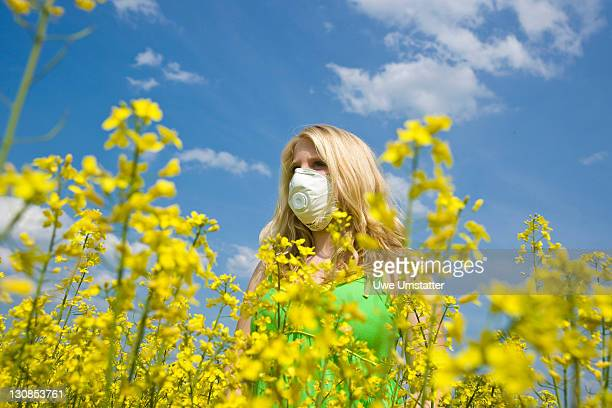 Blond girl wearing a face mask while standing in a field of rape