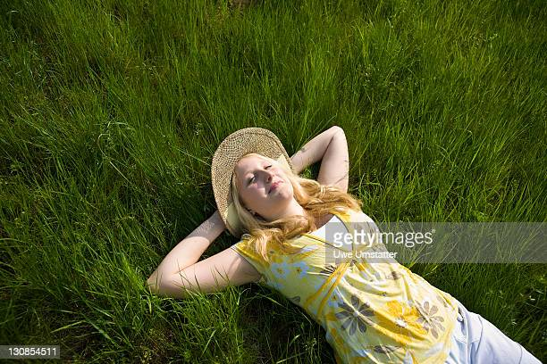 Blond girl wearing a hat, smiling while lying on a meadow
