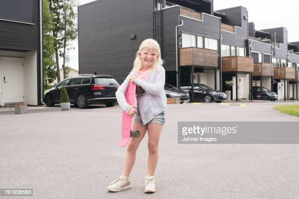 blond girl with pink skateboard on street - children only stock pictures, royalty-free photos & images