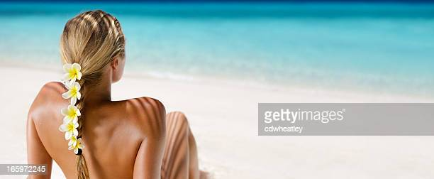 blond hair woman with yellow plumeria sunbathing at a beach