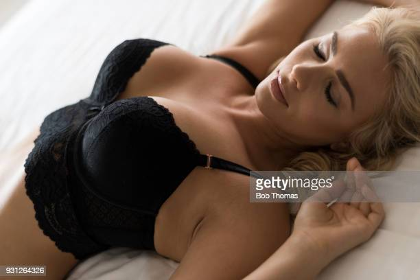 blond haired caucasian woman wearing lingerie lying down on a bed - bras stock pictures, royalty-free photos & images