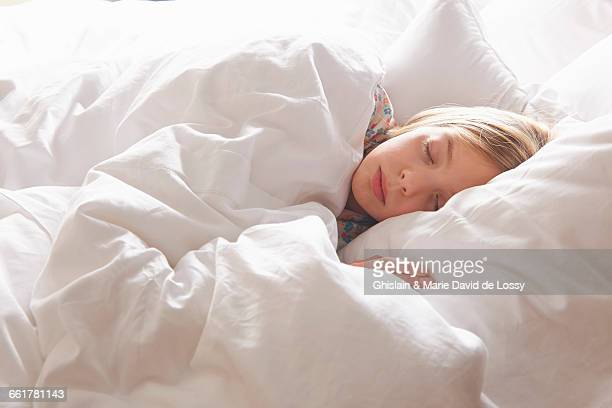 Blond haired girl asleep in bed