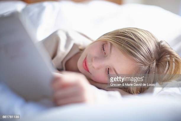 Blond haired girl lying in bed reading a book
