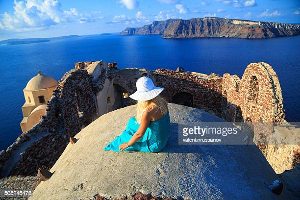 Blond haired woman with turquoise dress in Santorini, Greece.