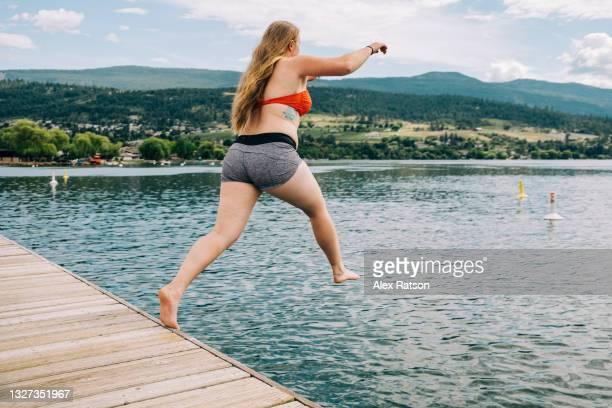 blond haired women jumps into kalamalka lake during the first week of summer - alleen volwassenen stockfoto's en -beelden