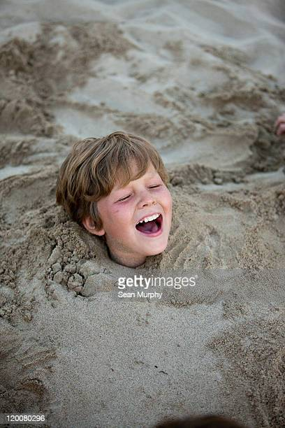 Blond kid buried in the sand