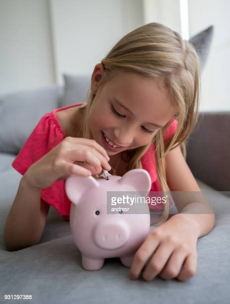 Blond little girl at home lying down on the couch inserting coins into her piggy bank