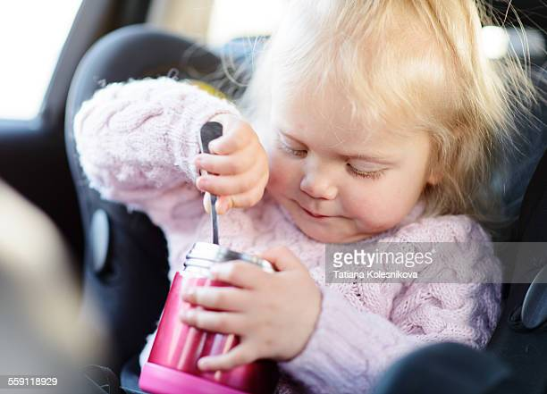 Blond little girl eating in the car seat