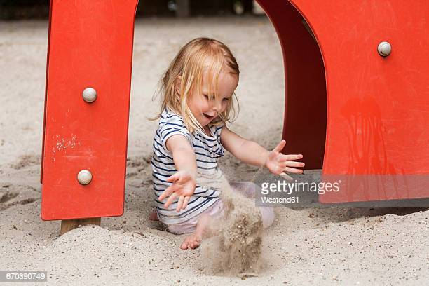 Blond little girl in sandbox on playground