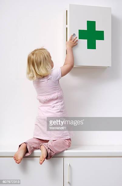 blond little girl opening medicine cabinet - armoire de toilette photos et images de collection