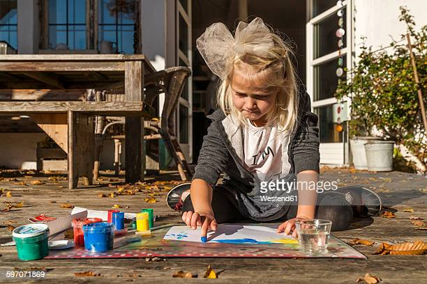 blond little girl painting with finger colours on the terrace - 4 girls finger painting stock photos and pictures