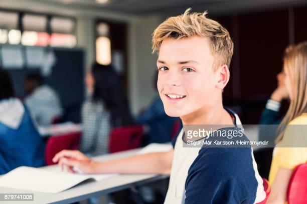 blond mannelijke tiener jongen zitten in klas - 14 15 jaar stockfoto's en -beelden