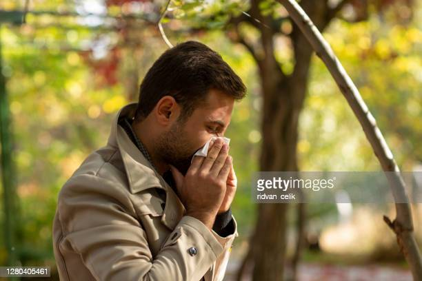 blond man outdoors blowing his nose - mucus stock pictures, royalty-free photos & images