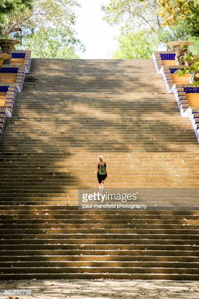 Blond mature lady walking up large concrete staircase