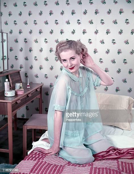 A blond model kneeling on a bed wearing a sheer light blue twopiece nightwear ensemble circa 1950