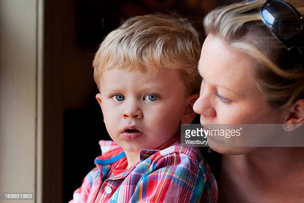 Blond mother and son sitting at window