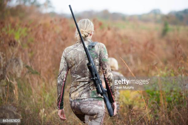 blond mother with rifle walking in field with child running ahead - rifle stock pictures, royalty-free photos & images