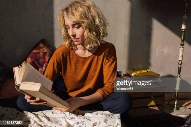 blond student sitting on bed reading a book - buch stock-fotos und bilder