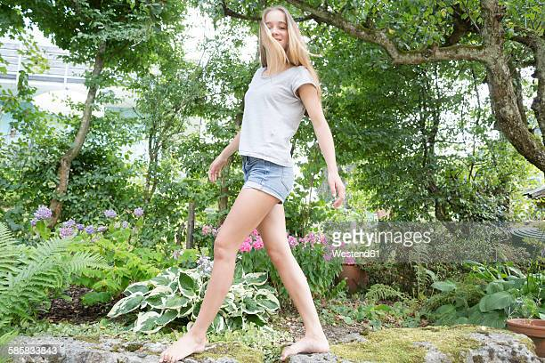blond teenage girl balancing on wall in a garden - ragazzine scalze foto e immagini stock