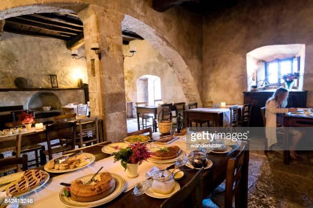 ブロンドの 10 代の少女は、サント ・ ステーファノ ・ ディ ・ セッサーニオ; の要塞化された中世の村、サント ・ ステーファノ ・ ディ ・ セクスタンティオの拡散のホテルで古代アーチ型ダイニング ルームで朝食を食べますグラン ・ サッソ国立公園;ラクイラ県、アブルッツォ州;イタリア;ヨーロッパ - アブルッツォ州 ストックフォトと画像