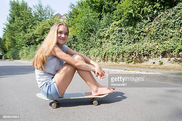 Blond teenage girl sitting on skateboard