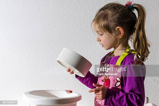 A blond three year old girl is baking Christmas cookies looking into a white bowl